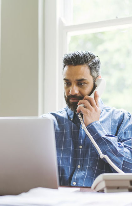 Mid adult businessman using laptop while talking on phone at home office. Serious man using wireless technology at desk. Male is working at home.
